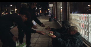 Two children handing out food to homeless